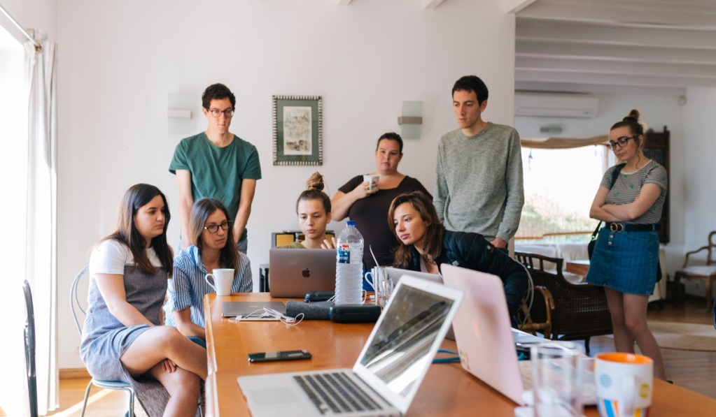 coworkers gathered around work table with manager